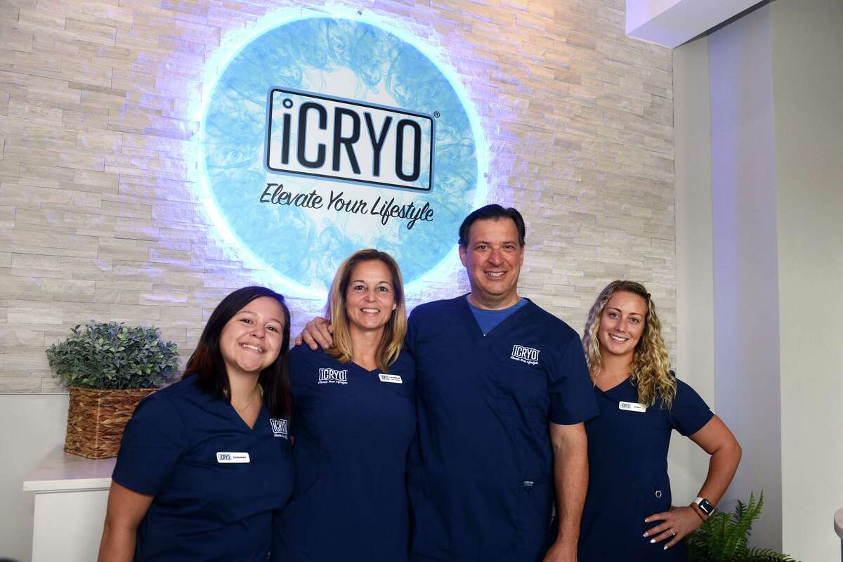 Gregg and Tracey Miller, center, pose with staff members Savannah Cruz, left, and Kaitlyn Alcamone at iCRYO Recovery & Wellness, in Fairfield, Conn. Aug. 17, 2021.