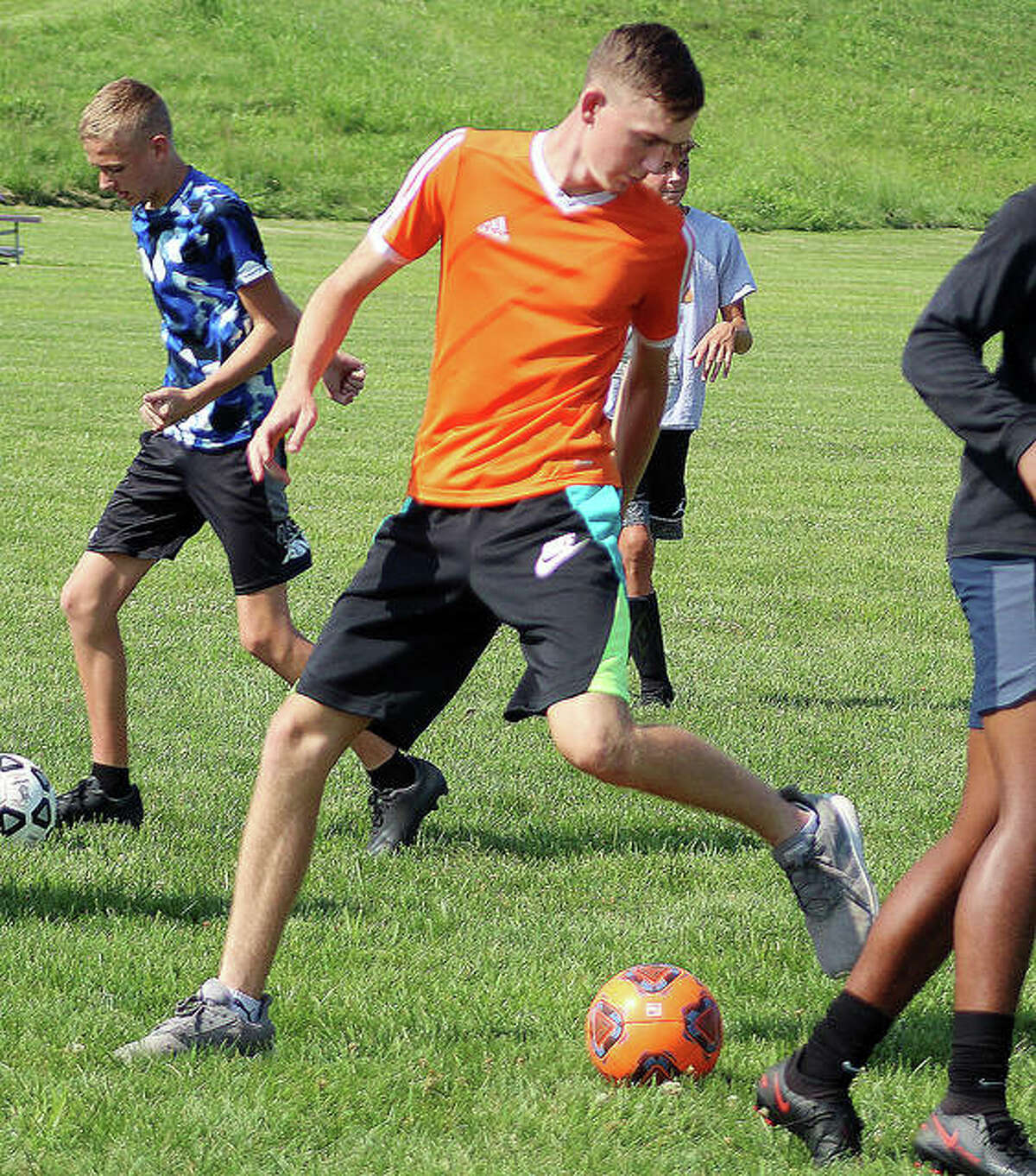EA-WR senior Carson Reef controls the ball in a crowd during his team's practice Tuesday at Wood River Soccer Park.
