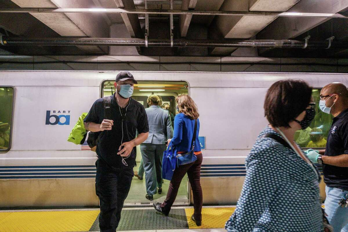 Riders are seen exiting and entering a BART train in San Francisco in early August. The TSA announced on Tuesday that masks must be worn while traveling on all mass transit and airplane services into January.