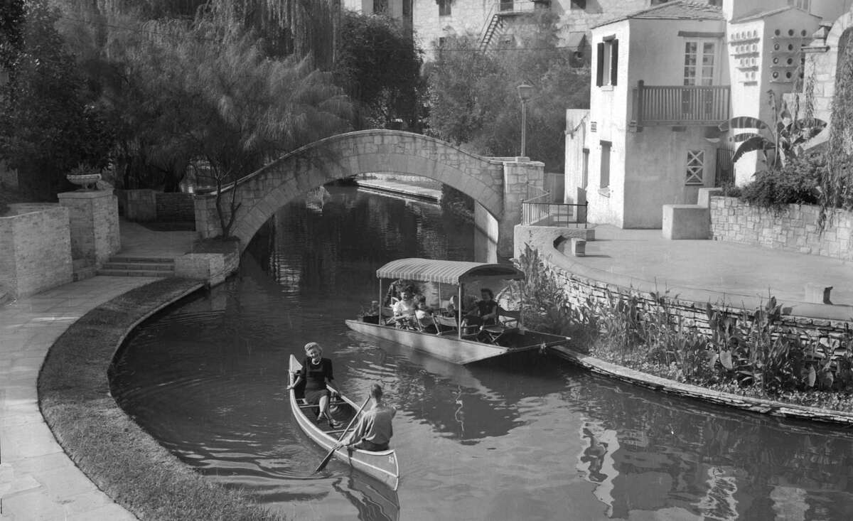 In this 1948 photo, a canoe shares the San Antonio River with a flat-bottomed boat in front of the Arneson River Theatre on the River Walk.