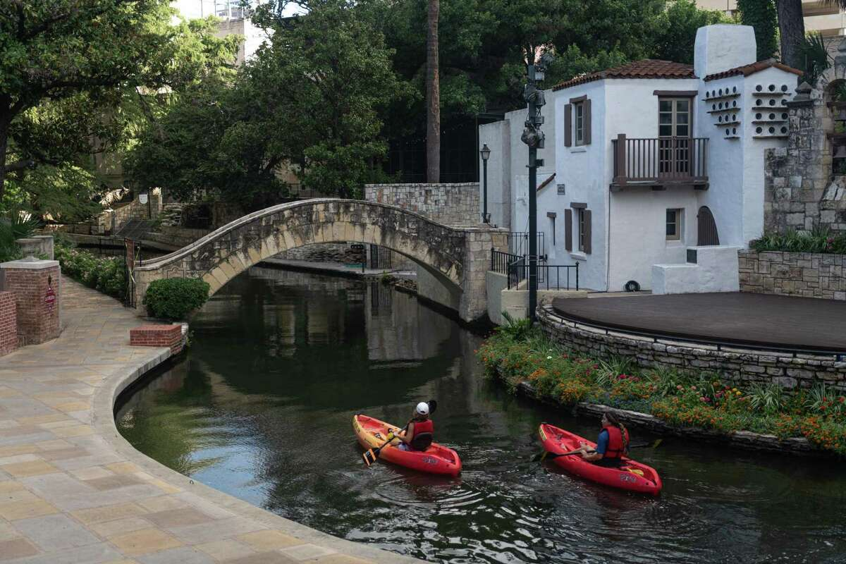 On a recent Friday morning, kayakers on the San Antonio River pass by the Arneson River Theatre as they paddle through the River Walk.