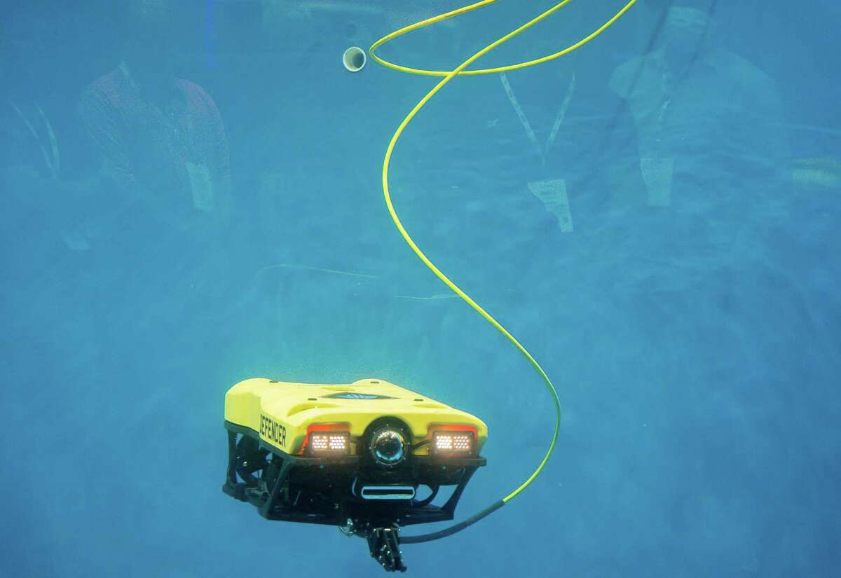 """VideoRay's remote operated underwater vehicle is demonstrated at OTC on Tuesday. """"Face to face always does better because of the human interaction,"""" Chris Gibson, VideoRay's vice president of sales, marketing and business development."""