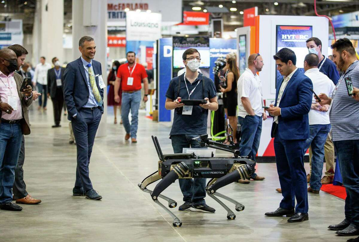 """Ghost Robotics head of special projects Tom Jacobs, center, conducts a demonstration of one of the company's robots on Tuesday at OTC. """"In-person is good for sales,"""" Jacobs said. """"People can see our videos online, but it doesn't compare to seeing it in person."""""""