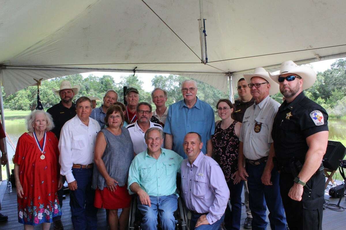 Gov. Greg Abbott poses with a group at an event in Austin County on Aug. 7, 2021.