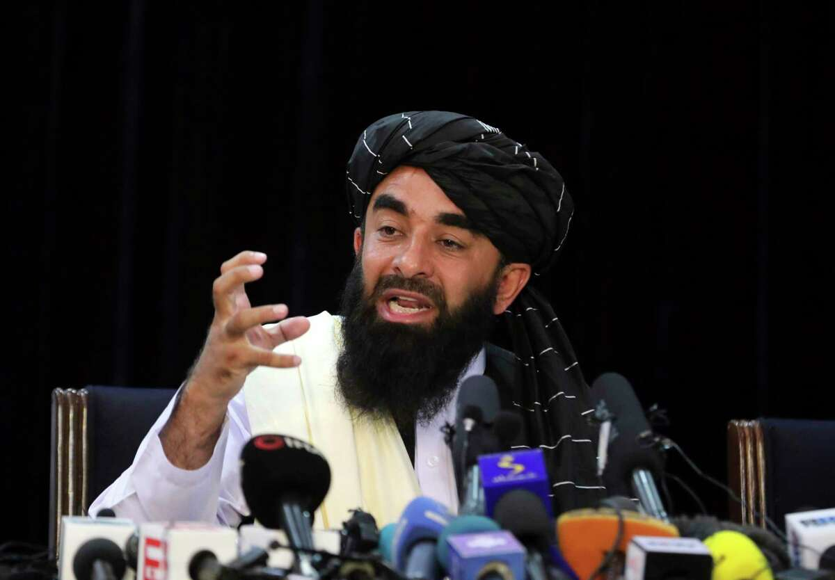 Taliban spokesman Zabihullah Mujahid speaks at his first news conference, in Kabul, Afghanistan, Tuesday, Aug. 17, 2021. For years, Mujahid had been a shadowy figure issuing statements on behalf of the militants. Mujahid vowed Tuesday that the Taliban would respect women's rights, forgive those who resisted them and ensure a secure Afghanistan as part of a publicity blitz aimed at convincing world powers and a fearful population that they have changed. (AP Photo/Rahmat Gul)