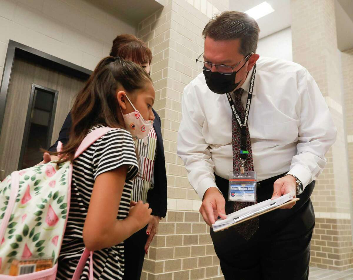 Conroe ISD Coordinator of Fine Arts Robert Horton helps a student find her way to her classroom on the first day of school at Conroe ISD's new Hope Elementary, Wednesday, Aug. 11, 2021. The district on Tuesday reported 610 active cases among its 64 campuses.