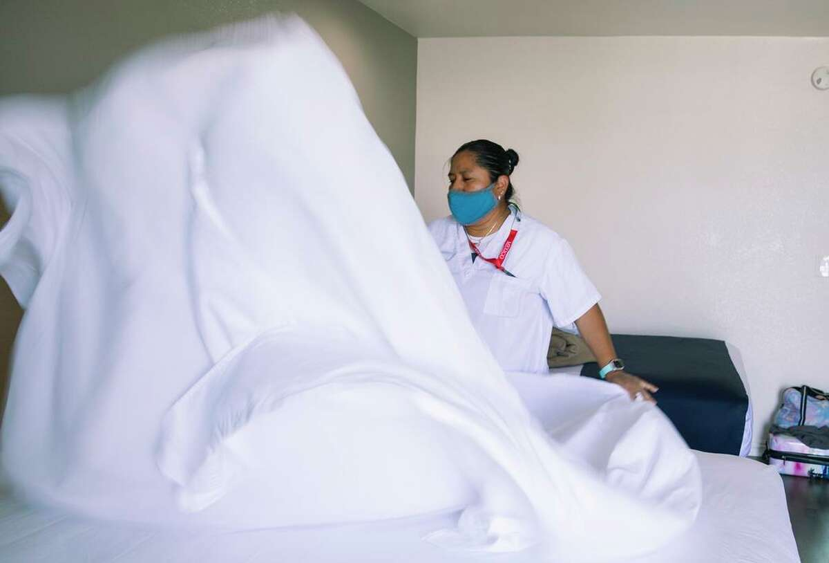 Claudia Chavez, a housekeeper at the Mission Inn, changes sheets in one of the rooms. The inn is one of four sites San Francisco is looking into buying and turning into housing for homeless people.
