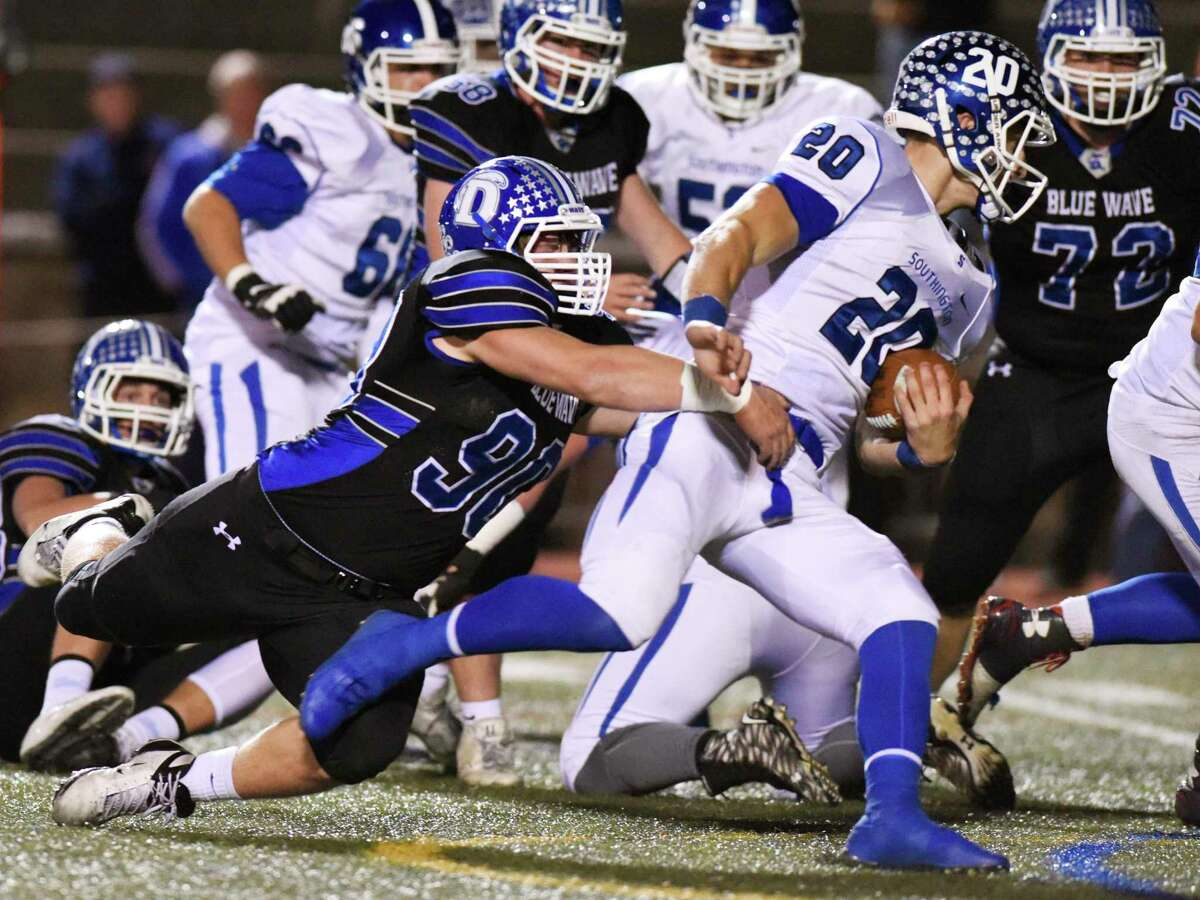 Darien defensive end Mark Evanchick (90) drags down Southington quarterback Jasen Rose (20) in the CIAC high school football tournament semifinal game between No. 2 Darien and No. 3 Southington at Boyle Stadium in Stamford, Conn. Monday, Dec. 7, 2015.