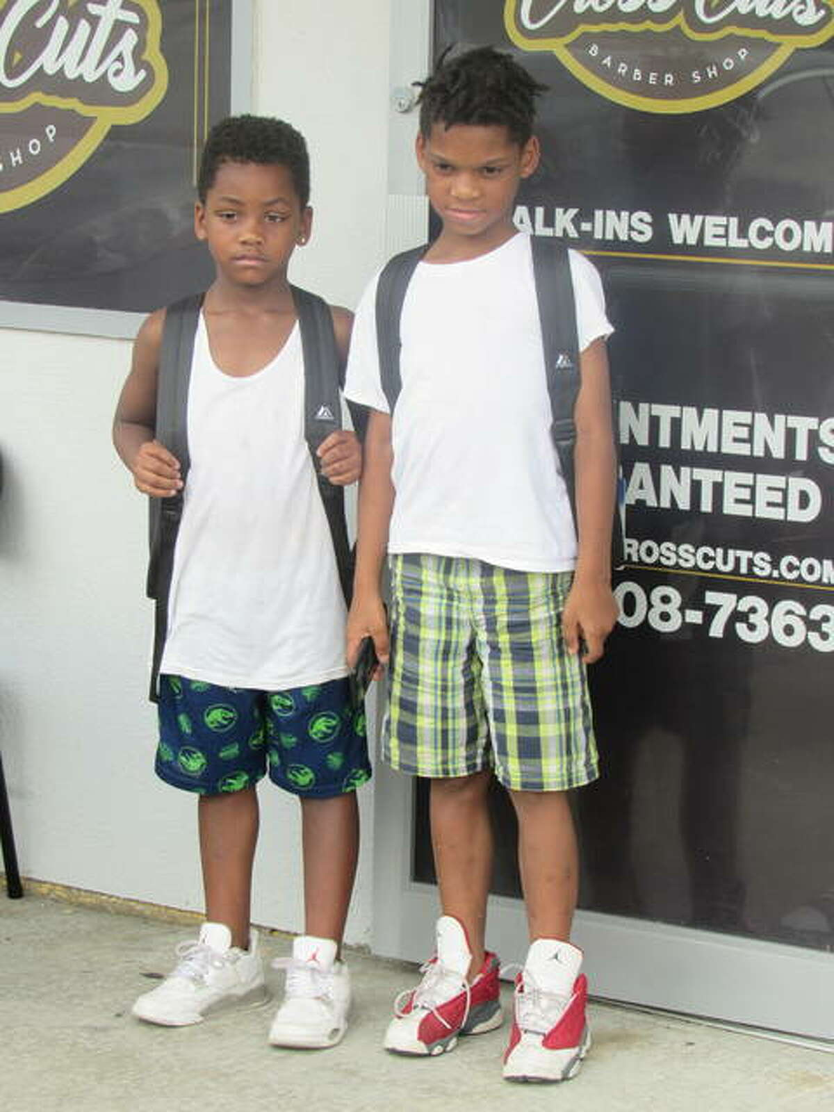 Two children wear their new backpacks.