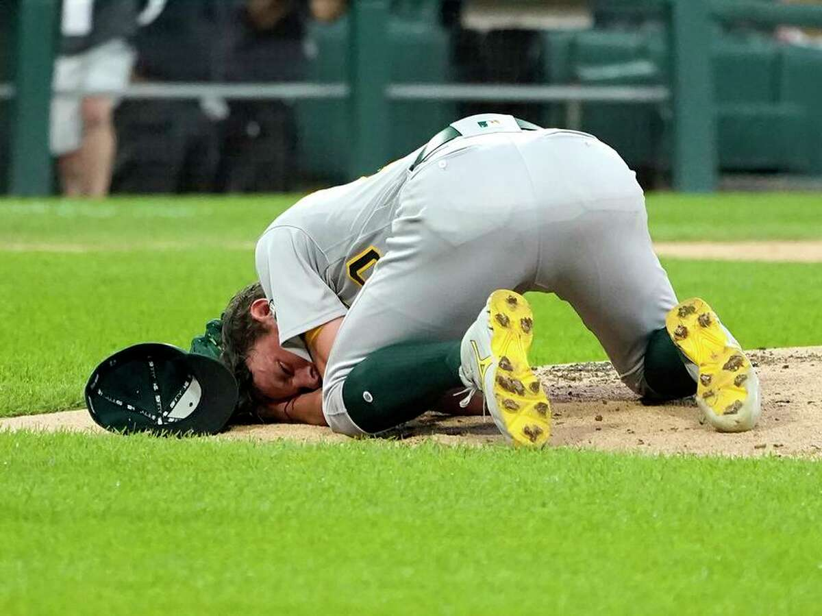 Oakland Athletics starting pitcher Chris Bassitt falls to the ground after getting hit in the head from a ball hit by Chicago White Sox's Brian Goodwin during the second inning of a baseball game, Tuesday, Aug. 17, 2021, in Chicago. (AP Photo/Charles Rex Arbogast)