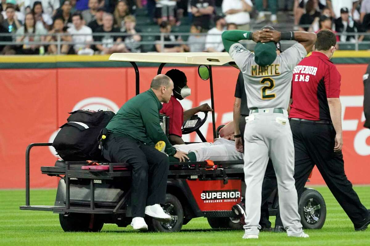 Oakland Athletics' Starling Marte (2) reacts as starting pitcher Chris Bassitt is taken off the field after being hit in the head by a ball hit by Chicago White Sox's Brian Goodwin during the second inning of a baseball game, Tuesday, Aug. 17, 2021, in Chicago. (AP Photo/Charles Rex Arbogast)