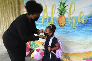 Raycela Campbell adjusts daughter Rose Truong's mask after the two took a photo together on the first day of school at Homer Drive Elementary. Photo made Tuesday, August 17, 2021 Kim Brent/The Enterprise