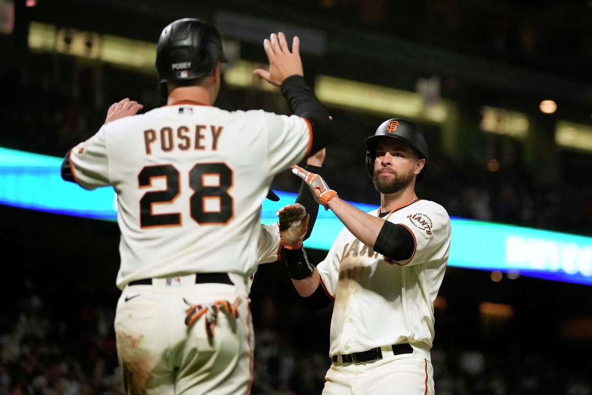 San Francisco Giants' Brandon Belt, right, high-fives Buster Posey (28) after hitting a three-run home against the Arizona Diamondbacks during the fifth inning of a baseball game Wednesday, June 16, 2021, in San Francisco. (AP Photo/Tony Avelar)