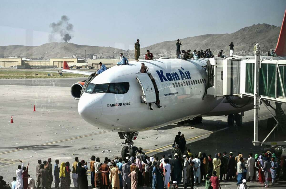 Afghan people climb atop a plane as they wait at the Kabul airport in Kabul on Monday, Aug. 16, 2021, after a stunningly swift end to Afghanistan's 20-year war, as thousands of people mobbed the city's airport trying to flee the Taliban's return. (Wakil Kohsar/AFP via Getty Images/TNS)