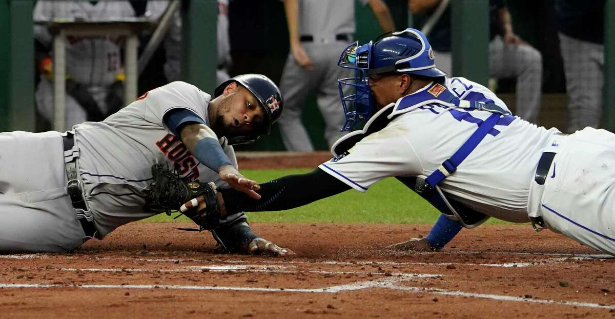 KANSAS CITY, MISSOURI - AUGUST 17: Martin Maldonado #15 of the Houston Astros is tagged out by Salvador Perez #13 of the Kansas City Royals as he tries to score on a Carlos Correa RBI single in the third inning at Kauffman Stadium on August 17, 2021 in Kansas City, Missouri.