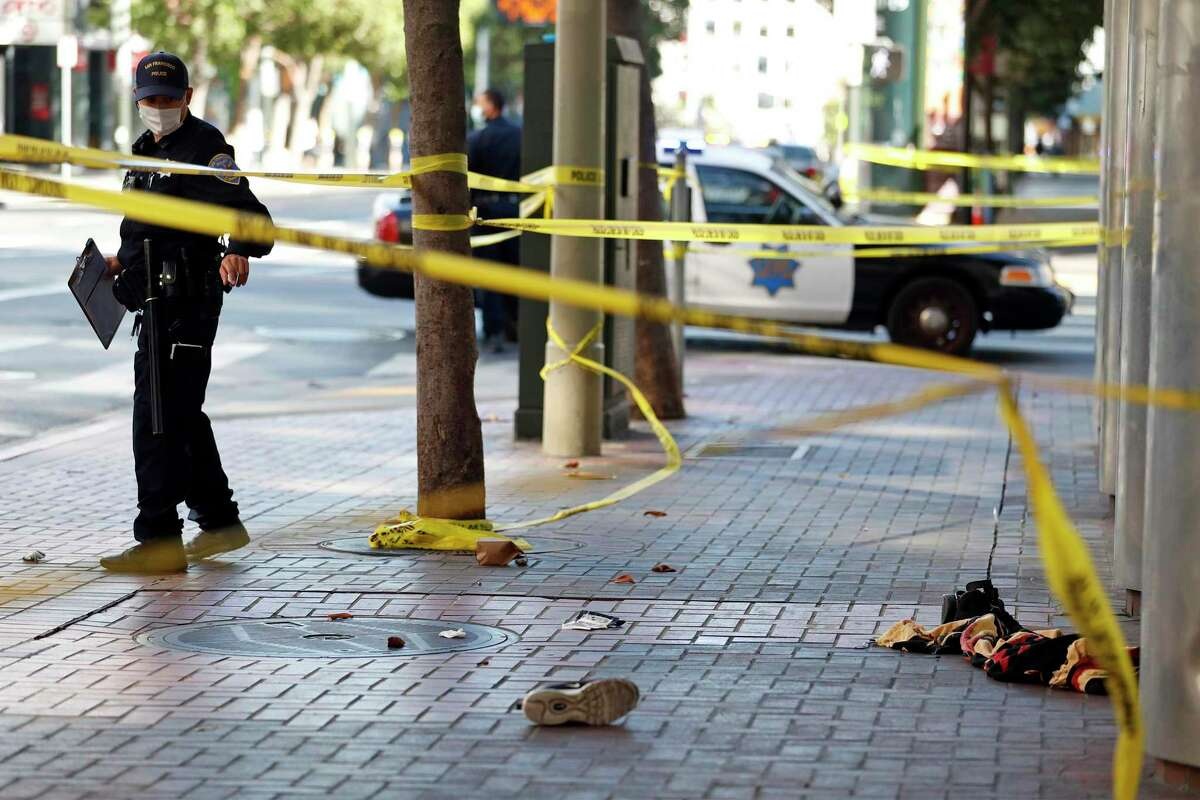 A San Francisco Police officer stands guard at the 4th Street scene of a shooting as a search for the shooting suspect goes on nearby at parking garage on Mission Street in San Francisco, Calif., on Wednesday, August 12, 2020.