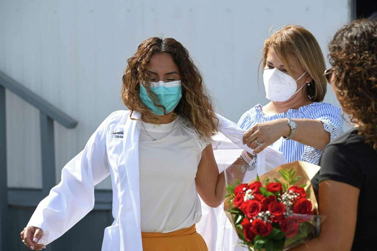 Samantha Sánchez, Directora del Centro Médico y de Bienestar de Empleados del Condado de Webb, se coloca su bata blanca con su madre y hermana, para conmemorar su trabajo, el martes 17 de agosto de 2021.