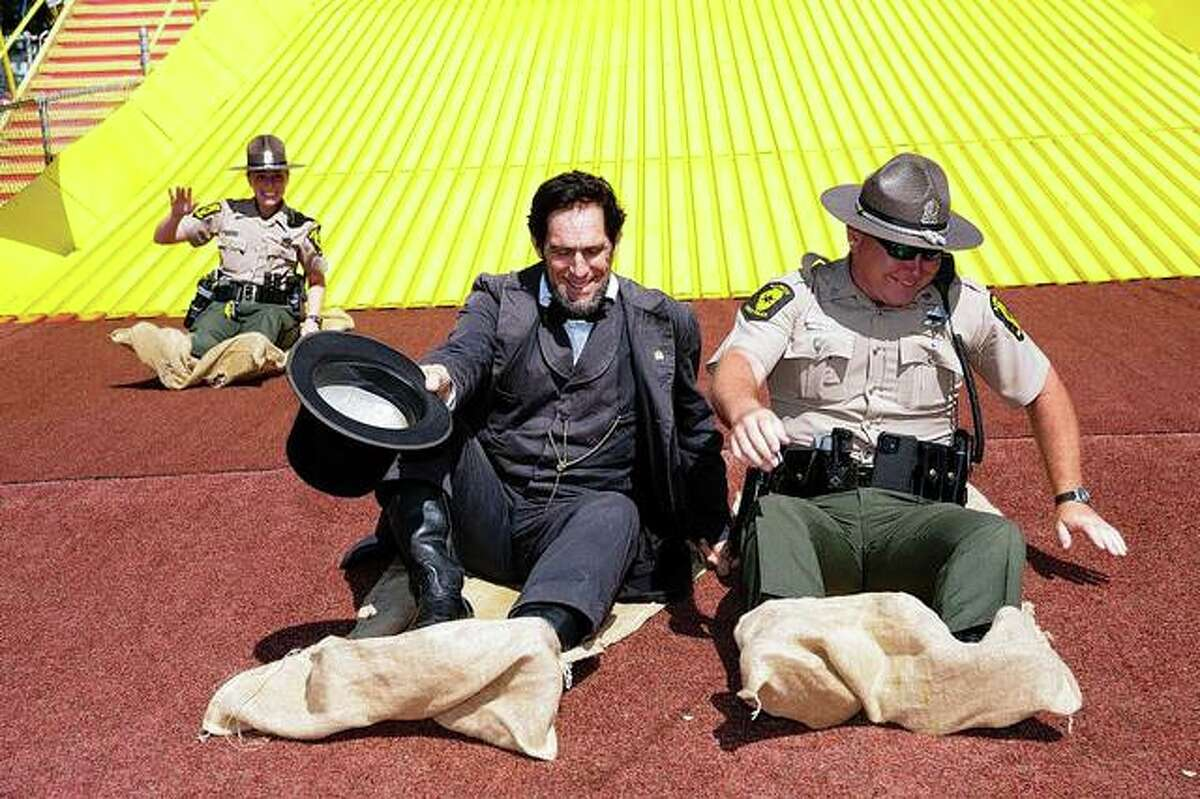 The race down the giant slide at the Illinois State Fair was a tie for at least one Illinois State Police trooper and an Abraham Lincoln portrayer.