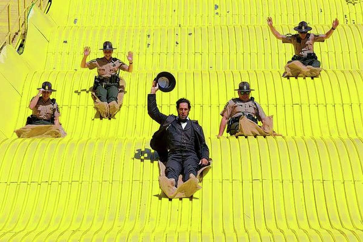 Five Illinois State Police troopers join an Abraham Lincoln portrayer as they hit the slopes of the Illinois State Fair's giant slide. It's become a tradition for President Lincoln to take a turn on the giant slide.