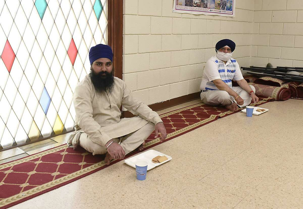 Bhai Gurpreet Singh, a priest, left, and Dr. Paul Uppal demonstrate how people will be social distancing at least six feet apart when they sit on carpet to eat when they hold services again at the Sikh Temple in Niskayuna, N.Y. During the pandemic and before, white supremacists and mass shooters targeted Sikhs who were easy to spot due to their turbans, a part of their attire imbued with religious significance since 1699,