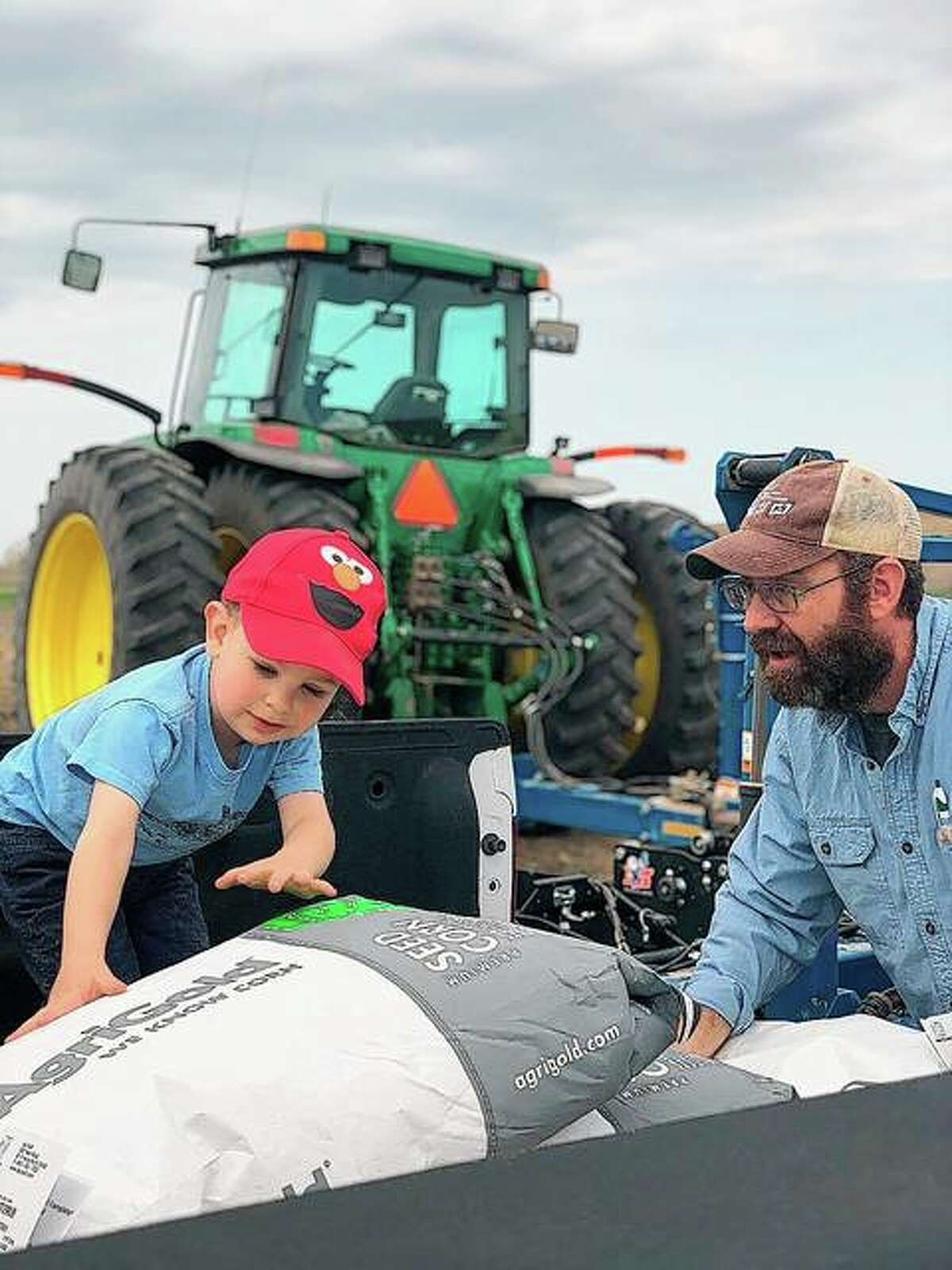 Tucker Coop helps his dad, Doug Coop, with planting at Coop Family Farm.