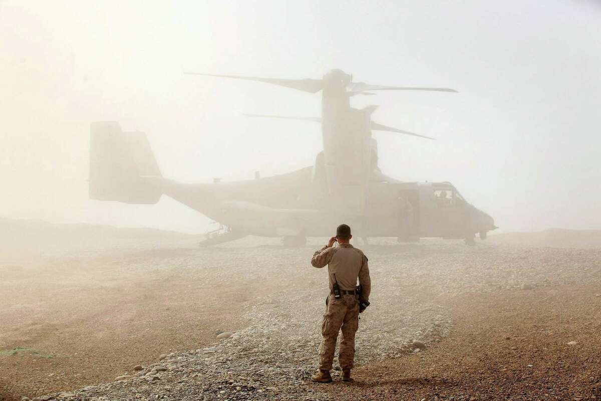 A U.S. Marine watches as an Osprey carrying Leon Panetta, the U.S. secretary of defense at the time, as he arrives March 14, 2012 at Forward Operating Base Shukvani, Afghanistan.