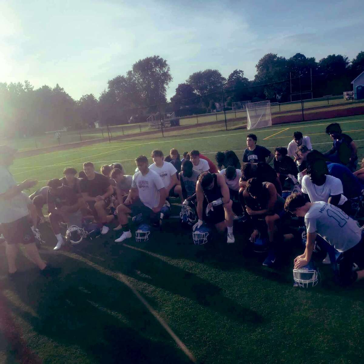 Rocky Hill kneels after its first day of conditioning on Monday, Aug. 16, 2021