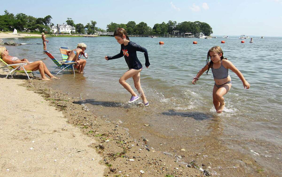 Victoria Yates, 8, center, and her friend Milly Allen, 7, run back their spot on the beach while enjoying the water at Weed Beach in Darien, Conn., on Wednesday June 30, 2021.
