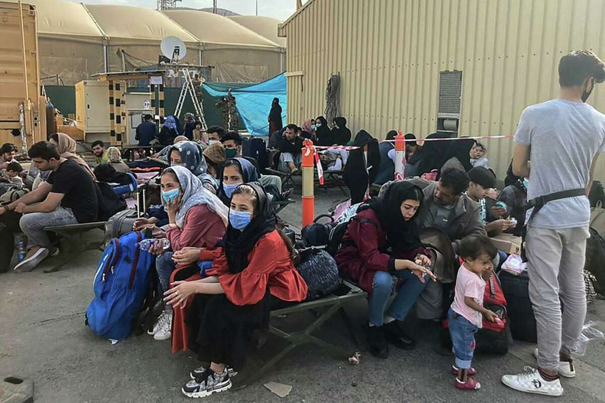 People wait to be evacuated from Afghanistan at the airport in Kabul on Aug. 18, 2021, following the Taliban takeover of the country.