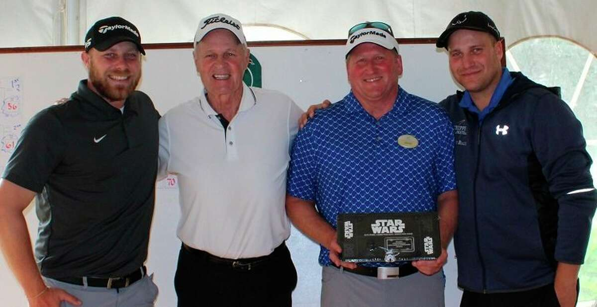 Winning Team (left to right):Manistee National PGA Professional Denis Meikle (3rd from left) jokingly presents a Star Wars license plate holder to the winning team of Alex Bialik, Jim Ogilvie, and Zach Bialik (not pictured: Mark Neisen). (Courtesy Photo)