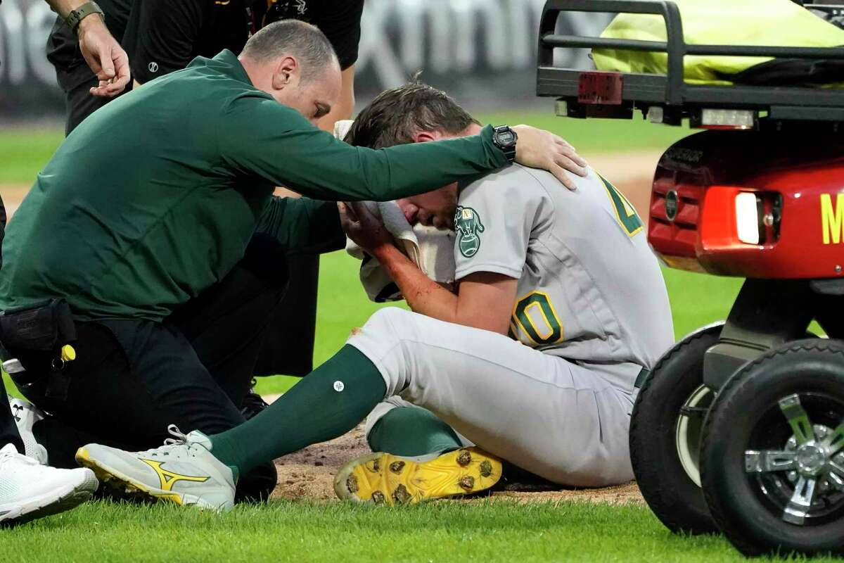 Oakland Athletics starting pitcher Chris Bassitt is attended to after getting hit in the head from a ball hit by Chicago White Sox's Brian Goodwin during the second inning of a baseball game, Tuesday, Aug. 17, 2021, in Chicago. (AP Photo/Charles Rex Arbogast)