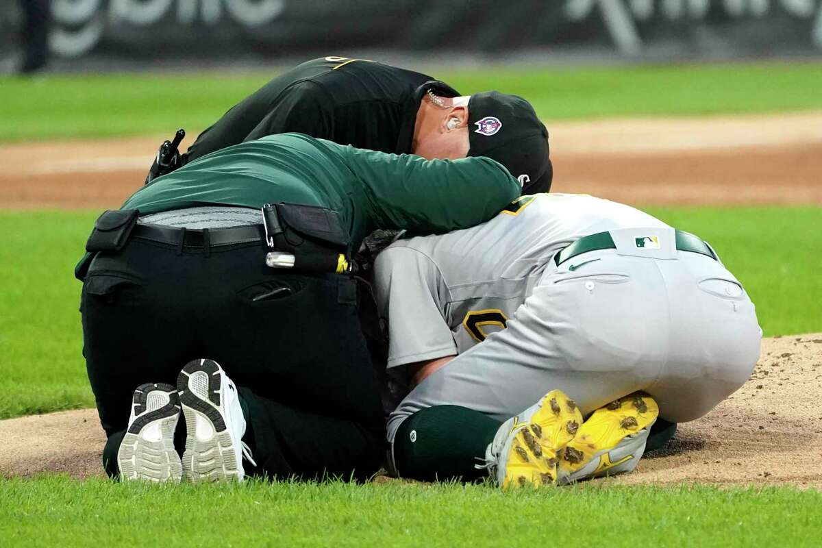 Oakland Athletics starting pitcher Chris Bassitt receives immediate medical attention after getting hit in the head by a ball hit by Chicago White Sox's Brian Goodwin during the second inning of a baseball game Tuesday, Aug. 17, 2021, in Chicago. (AP Photo/Charles Rex Arbogast)