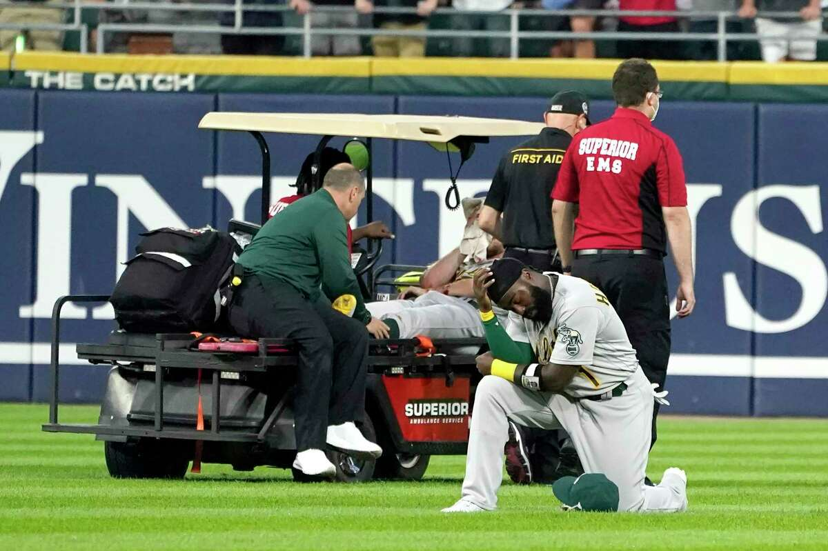 Oakland Athletics' Josh Harrison reacts as starting pitcher Chris Bassitt is taken off the field after Bassitt was hit in the head by a ball hit by Chicago White Sox's Brian Goodwin during the second inning of a baseball game, Tuesday, Aug. 17, 2021, in Chicago. (AP Photo/Charles Rex Arbogast)