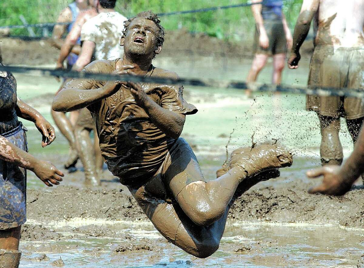 """A Bristol man competes for the """"Swamp Rats"""" during the 16th annual Mud Volleyball Tournament to support the Epilepsy Foundation of Connecticut at Zoar Pond in Middletown."""