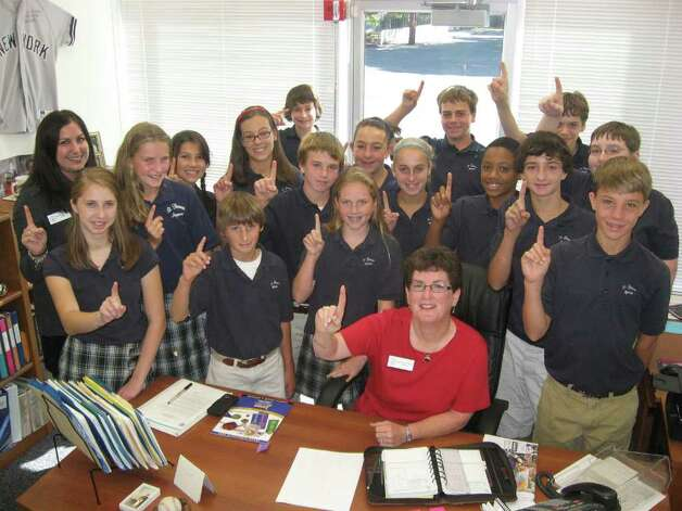 Pictured is Pat Brady, principal of St. Thomas Aquinas School, along with Jennifer Oligino's 8th grade science class. St. Thomas was recently recognized by the United States Department of Education as a 2010 Blue Ribbon School. The award honors public and private elementary, middle and high schools whose students achieve at very high levels or have made significant progress and helped close gaps in achievement especially among disadvantaged and minority students. Photo: Kirk Lang / Fairfield Citizen