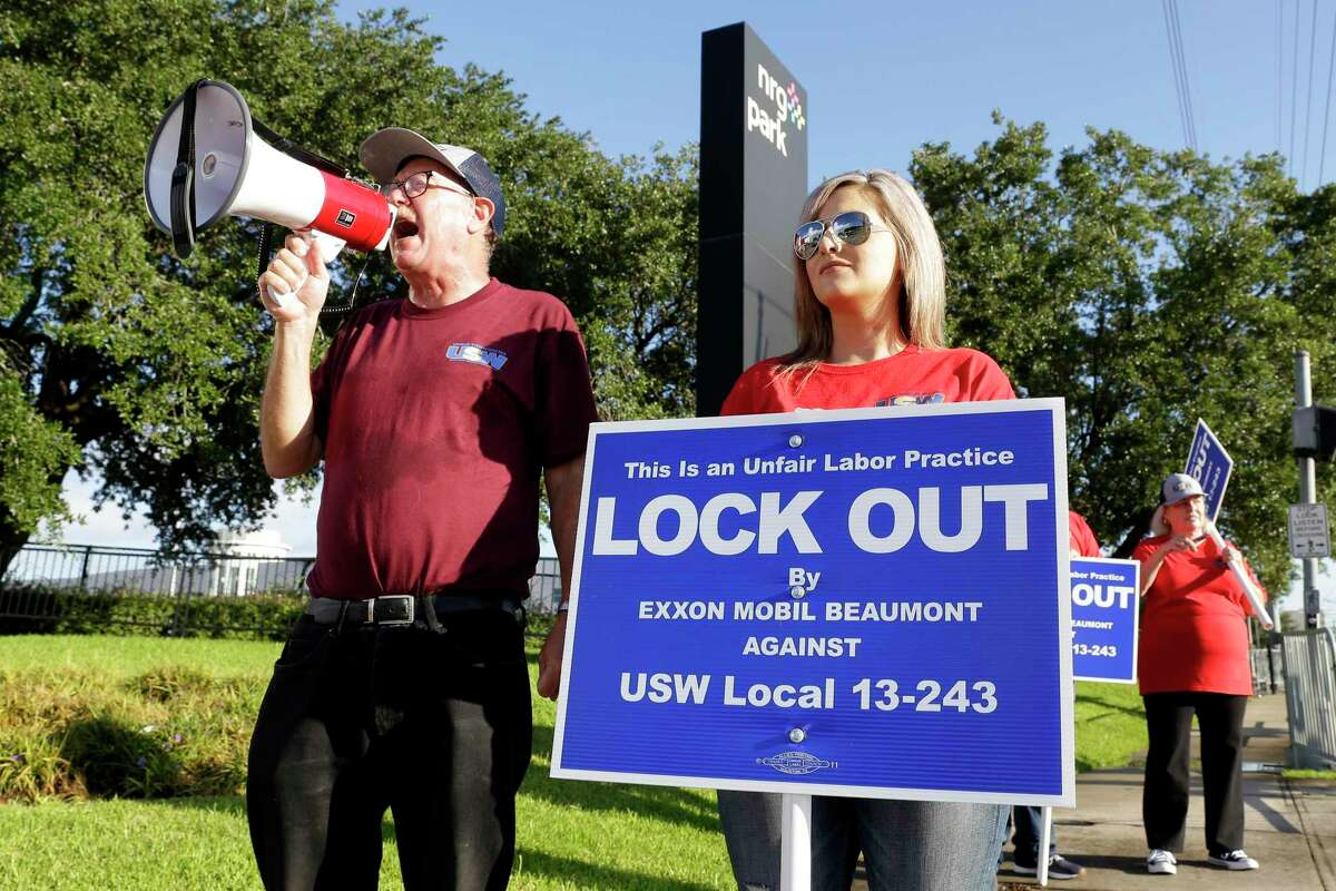 Mike Zielinski, with bullhorn, and Ashley Melton, right, along with some 30 other United Steel Worker union members from both Beaumont and Houston stage a protest on the east side of NRG Park against the lockout at Exxon Mobil located in Beaumont, TX, Wednesday, Aug. 18, 2021 during the Offshore Technology Conference in Houston, TX.