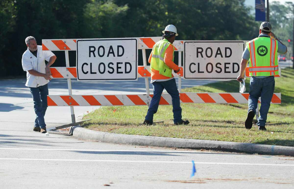 Workers with the San Jacinto River Authority close the east bound section of Research Forest Drive near New Trails Drive to begin repairs on a 30-inch surface water transmission line, Wednesday, Aug. 18, 2021, in The Woodlands.