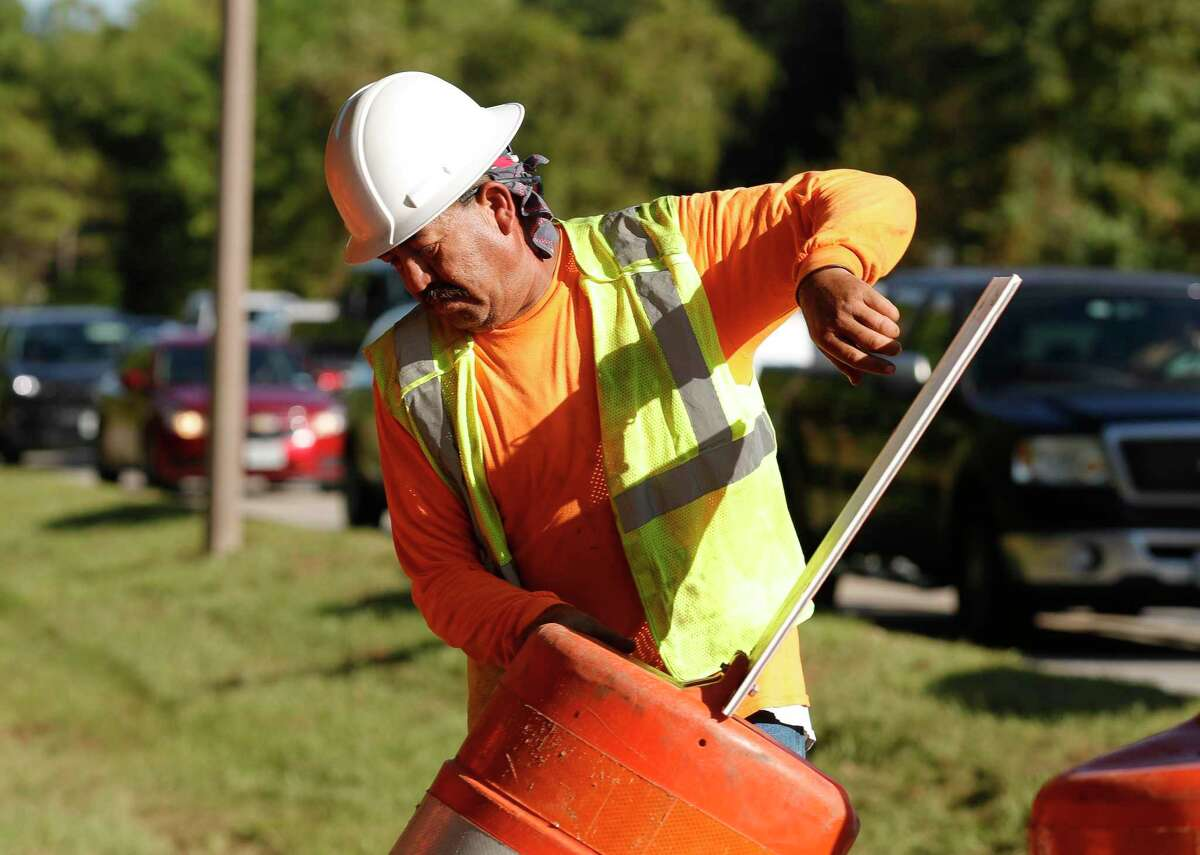 A worker with the San Jacinto River Authority moves a construction barrel as traffic backs up on Research Forest Drive, Wednesday, Aug. 18, 2021, in The Woodlands. East bound traffic was rerouted repairs to a 30-inch surface water transmission line near New Trails Drive began.