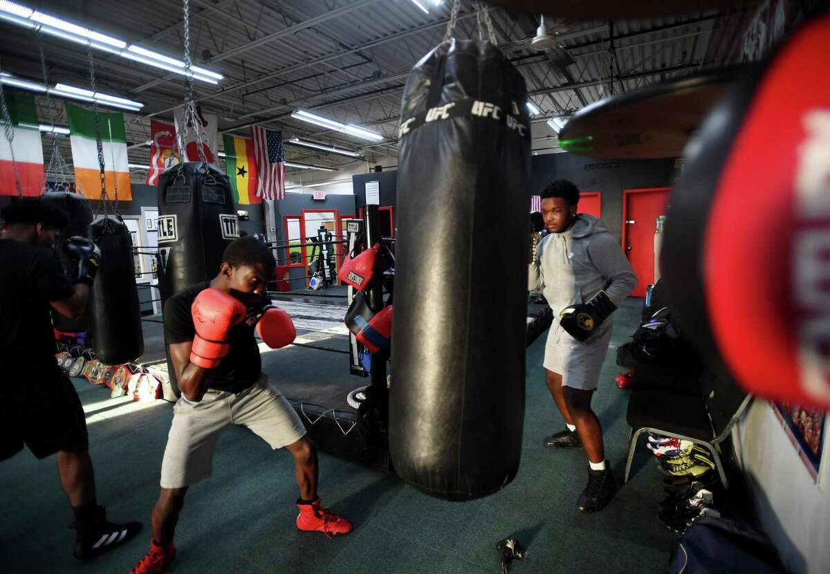 Christopher Alexis, 16, left, and Isaiah Haynes,16, both of Stratford, hit the heavy bag with their fellow boxers at the Chick Rosnick Boxing Club in Stratford, Conn. on Monday, August 16, 2021.