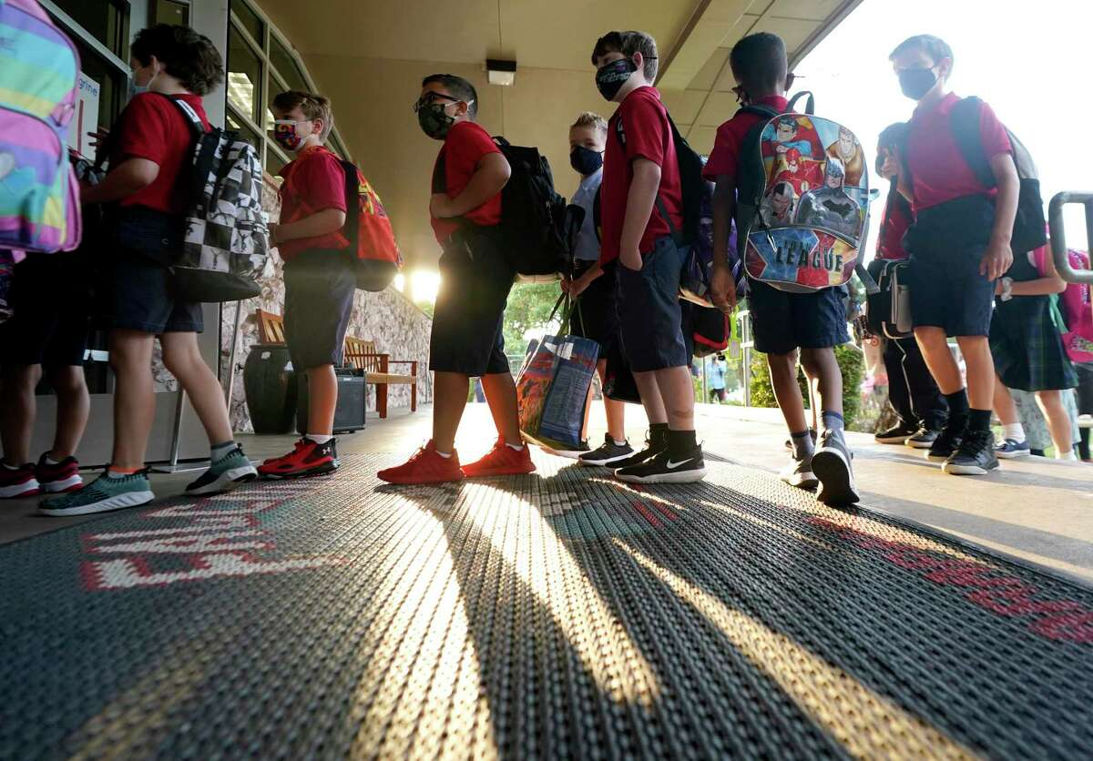 Wearing masks to prevent the spread of COVID-19, elementary school student line up to enter school for the first day of classes in Richardson, Texas, Tuesday, Aug. 17, 2021. Despite Texas Gov Greg Abbott's executive order banning mask mandates by local officials, the Richardson Independent School District and many others across the state are requiring masks for students. (AP Photo/LM Otero)