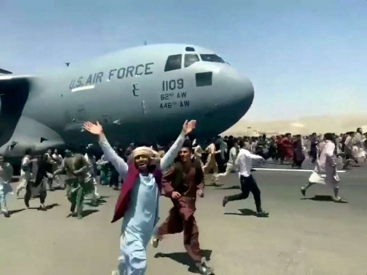 Hundreds of people run alongside a U.S. Air Force C-17 transport plane as it moves down a runway of the international airport, in Kabul, Afghanistan, Monday, Aug.16. 2021. Thousands of Afghans have rushed onto the tarmac of Kabul's international airport, some so desperate to escape the Taliban capture of their country that they held onto an American military jet as it took off and plunged to death.