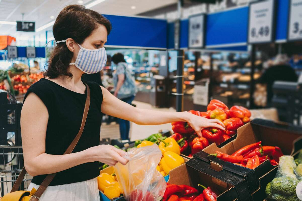 Woman grocery shopping with a protective face mask on during the pandemic.