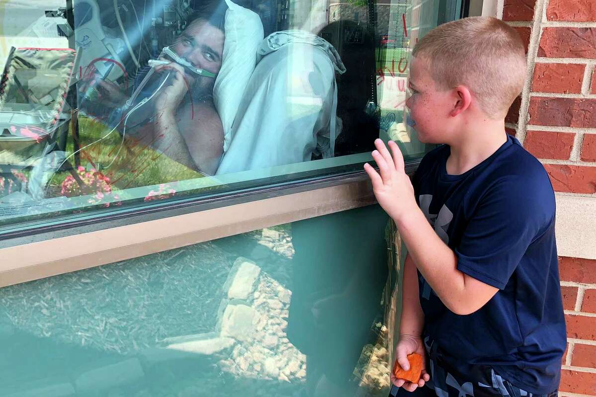 FILE - In this July 26, 2021, file photo, Brody Barker waves to his father, Daryl, from outside his hospital room in Osage Beach, Mo., as he recovers from COVID-19. Many overwhelmed hospitals, with no beds to offer, are transporting critically ill COVID-19 patients hundreds of miles to far-flung states for treatment. The delta variant of the virus, combined with low vaccination rates in many states, is causing a surge that has hospitals scrambling to find bed space.