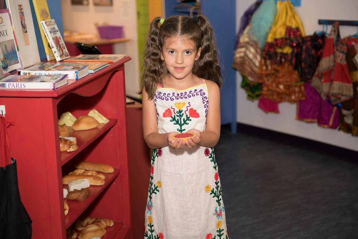 A child poses with their work after an activity (Credits: World Awareness Children's Museum)