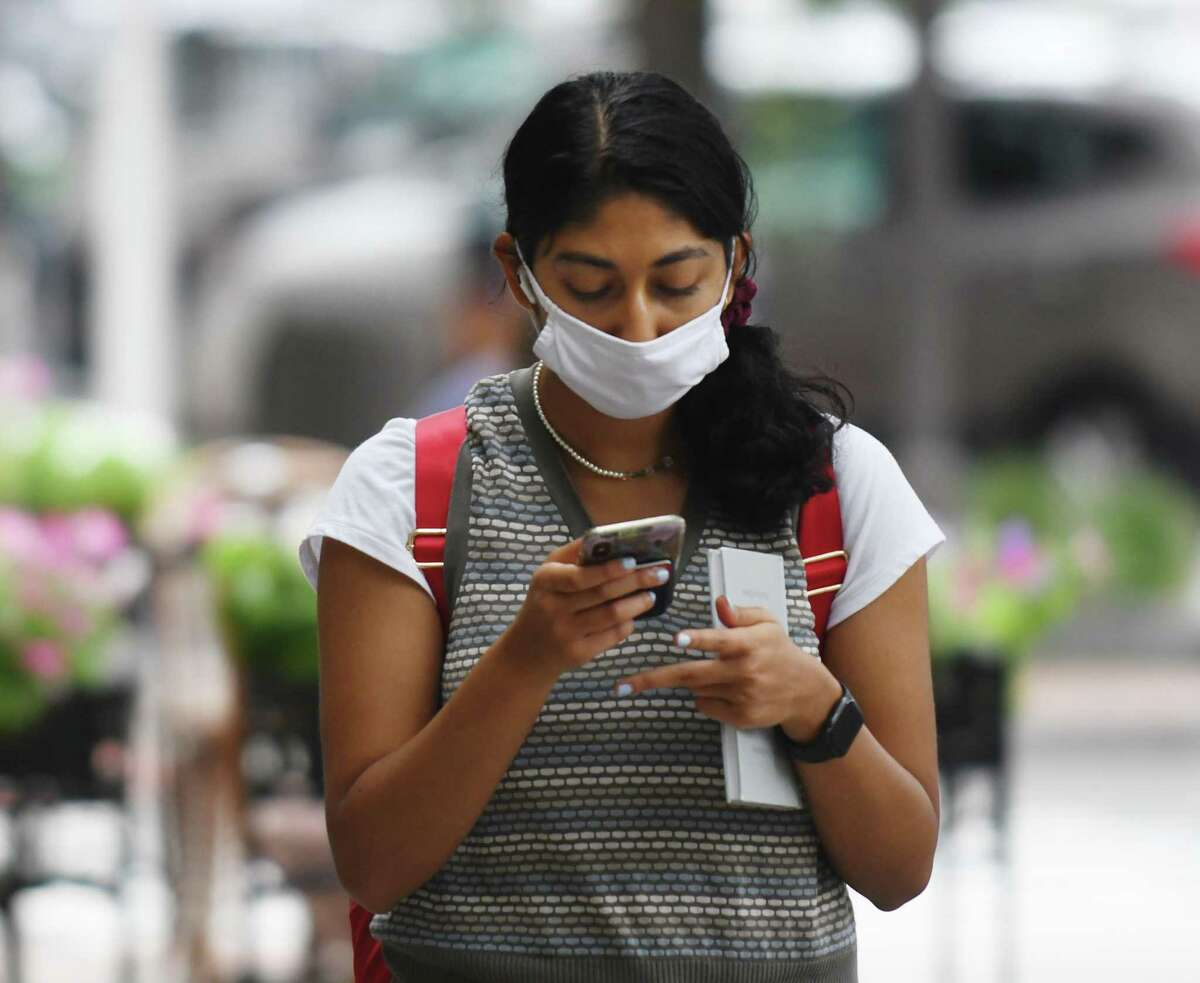 Stamford's Anya Bhogte wears a mask while walking down Bedford Street in Stamford, Conn. Tuesday, Aug. 10, 2021. Elected officials with the Southeastern Connecticut Council of GovernmentsElected are asking Gov. Ned Lamont to enact a statewide indoor mask mandate.
