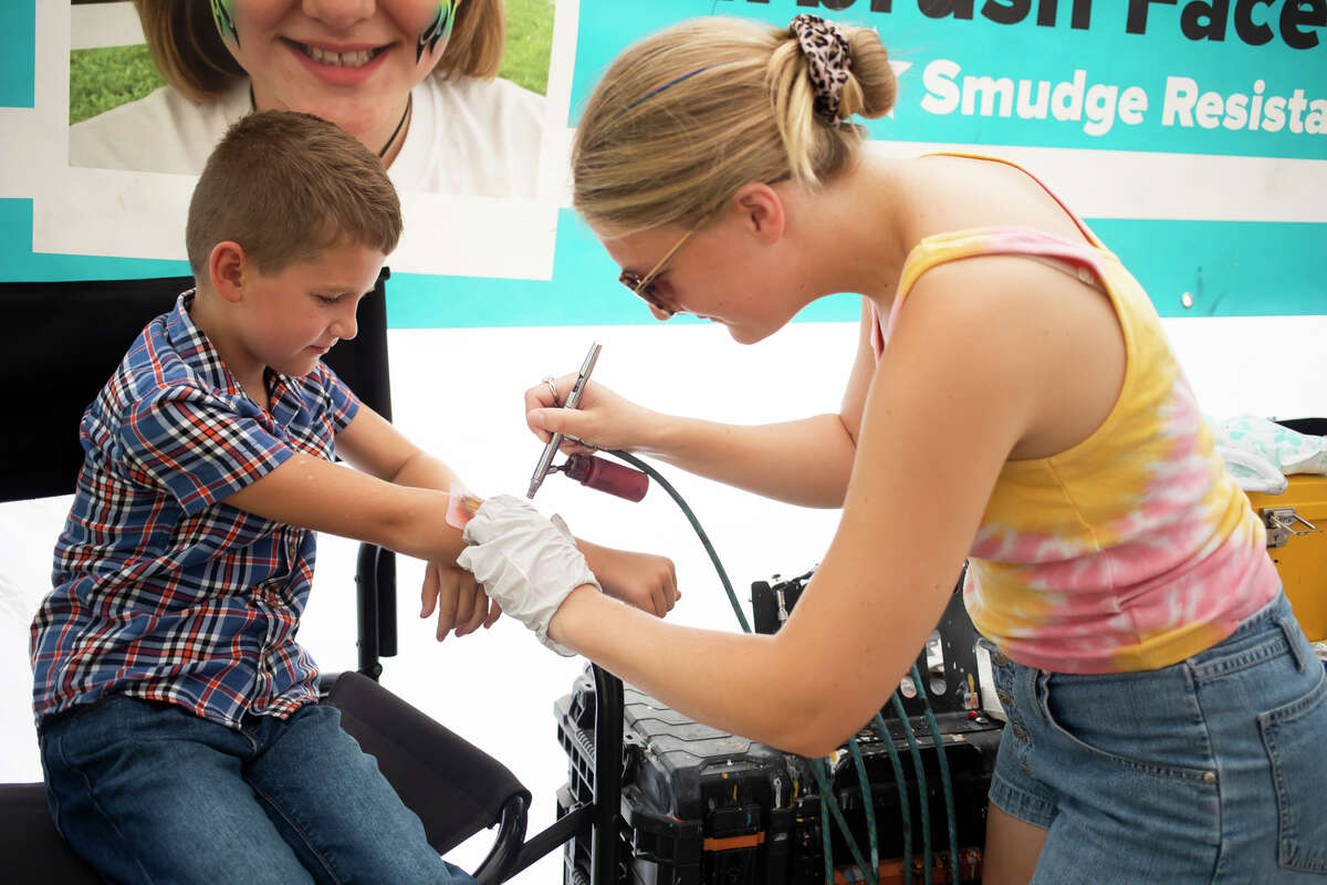 Kellin Colpean of Midland, 7, gets an airbrush tattoo at the Modern Ink Body Art tent Wednesday, Aug. 18, 2021 at the Midland County Fair, which continues through Saturday. (Katy Kildee/kkildee@mdn.net)