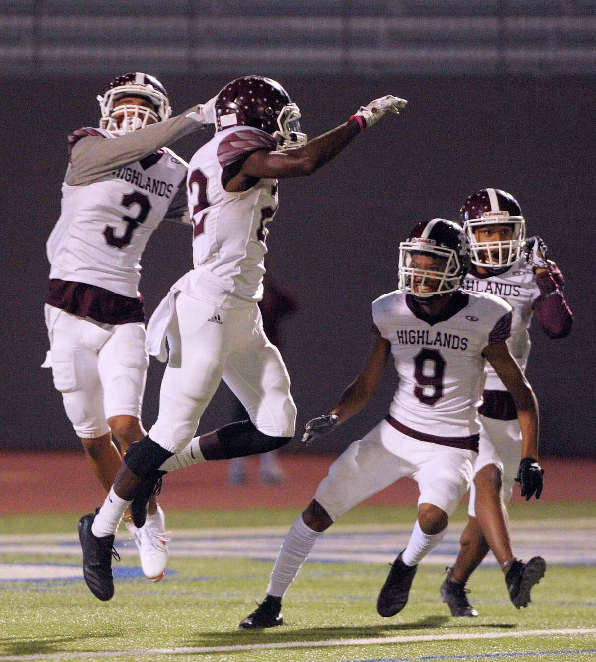 D'Marrion Gonzales, second from left, of Highlands, is mobbed by teammates Dre'Chan Moody (3) and Eric Rodriguez (8) after scoring on the opening kickoff against Brackenridge during high school football action at Alamo Stadium on Thursday, Nov. 8, 2018.