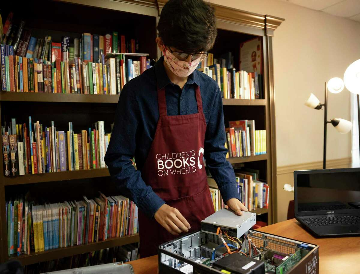 Jinesh Jain junior at The Woodlands High School prepares to replace the ram sticks in a donated desktop at the Sleepy Hollow Multipurpose Building in Tamina, Wednesday, August 12, 2020. Children's Books On Wheels in partnership with Jain will refurbish old laptops and desktops for children in need of computers. The Jain family will be honored by CBOW on Aug. 28 at its annual Dress White Linen Night.