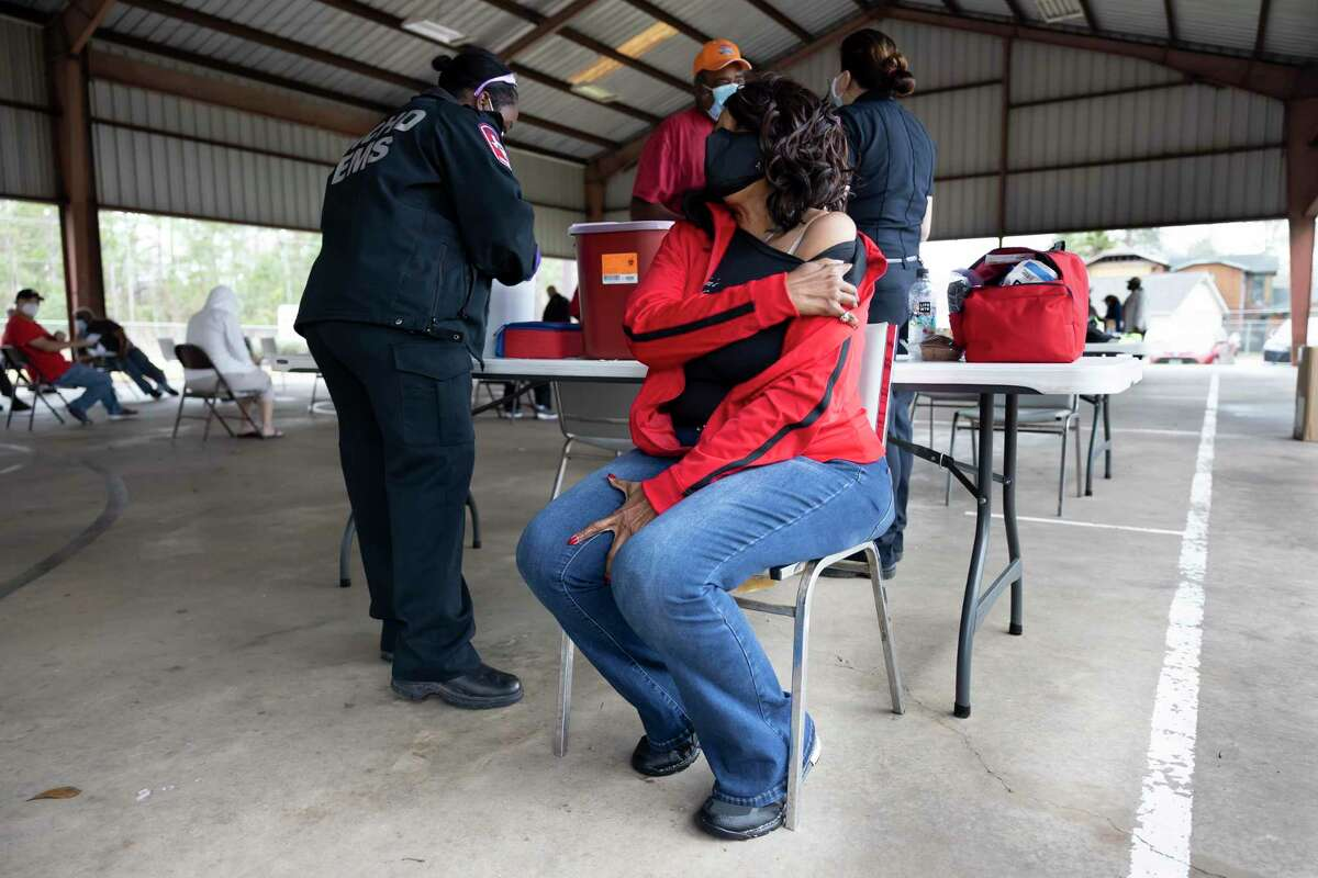Rita Wiltz, center, holds down her shoulder sleeve as she prepares to take the Moderna COVID-19 vaccination at the Tamina Community Park, Saturday, Jan. 23, 2021, in Tamina. An estimated 280 doses of the vaccine were distributed at the event. The site was in partnership with the Montgomery County Office of Emergency Management and the Lone Star Family Health Center.