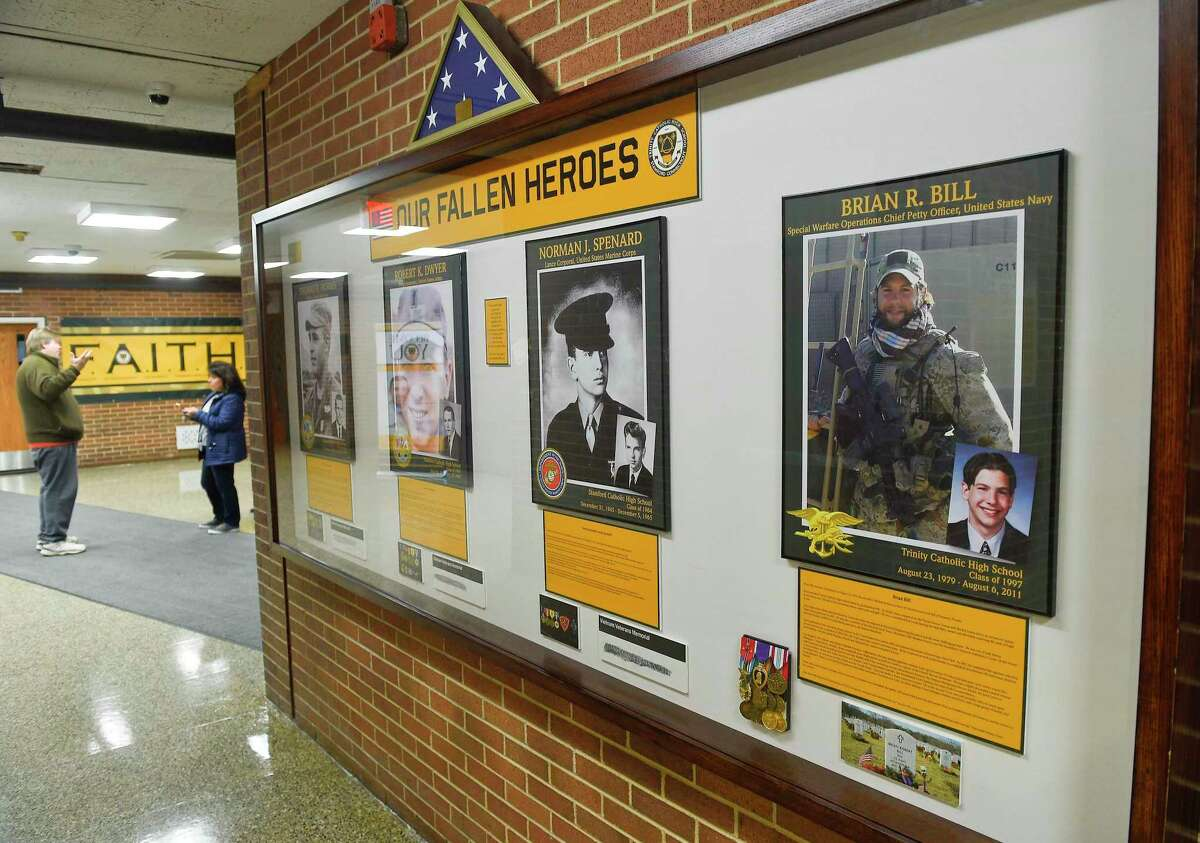 A portrait of Brian R. Bill, Special Warfare Operations Chief Petty Officer, United States Navy, a Trinity High School Class of 1997 alumni who perished in combat in Afghanistan on August 6, 2011, is displayed among Fallen Heroes in a hallway near the gymnasium at the Catholic high school in Stamford, Connecticut on Feb. 25, 2020.